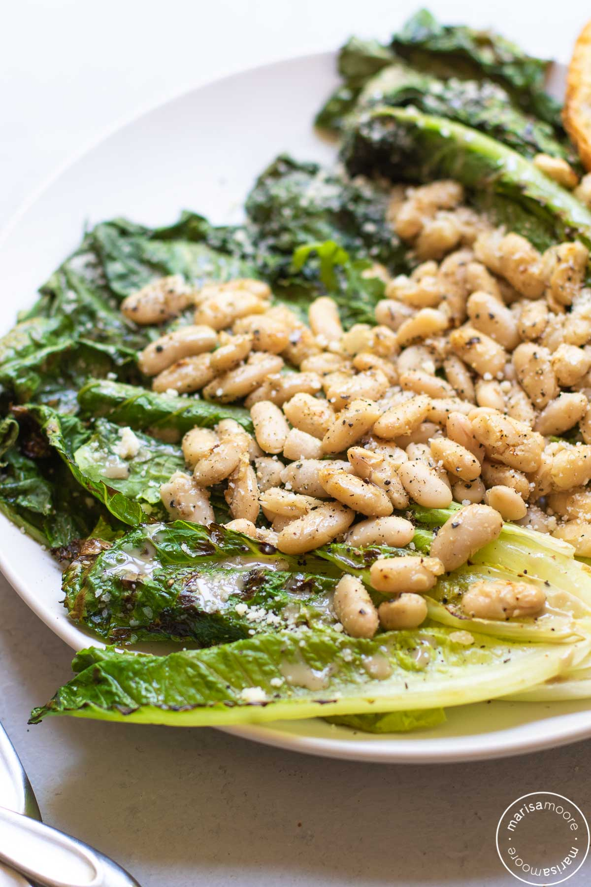 Whole leaves grilled lettuce with white beans on top on a white plate