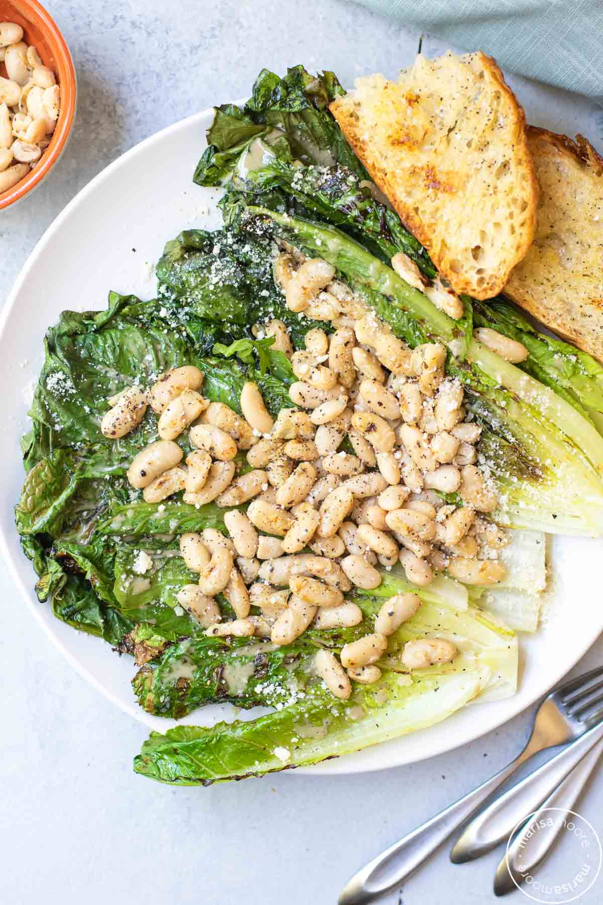 White Bean Salad over grilled lettuce with crusty grilled bread on a white plate