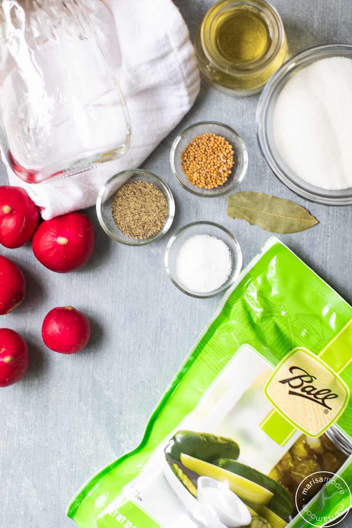 radishes, pickling salt, sugar, vinegar, and spices on a grey board