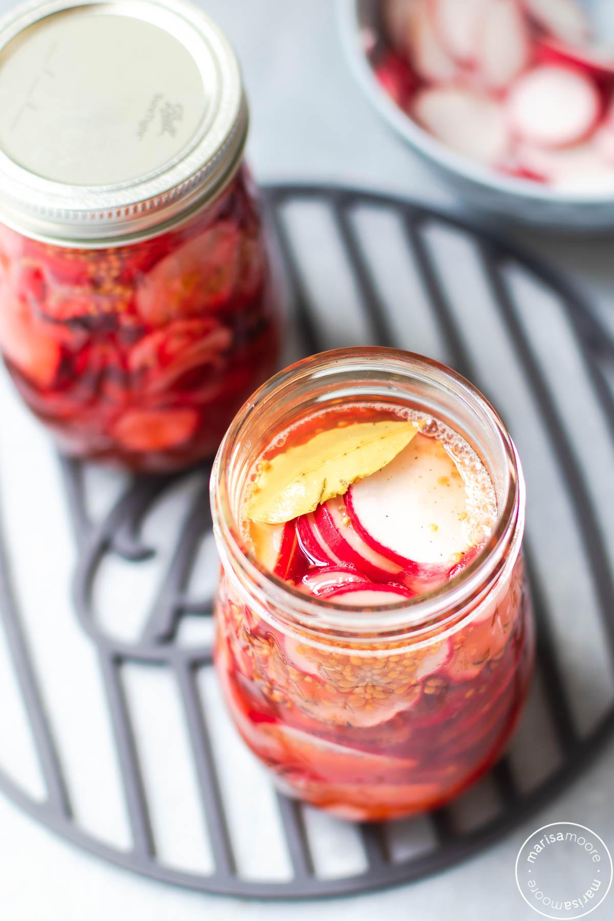 Overhead shot of radishes in brine in jars