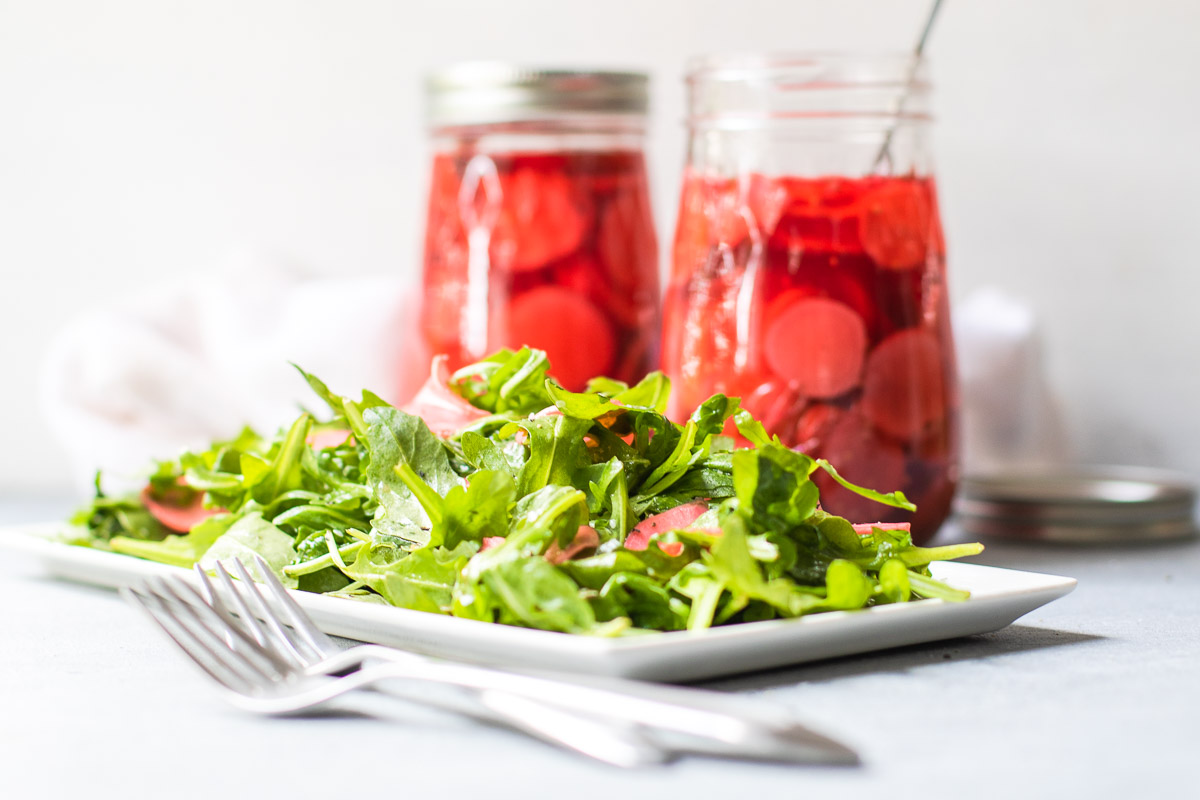 Green salad with two jars of quick pickles and two forks