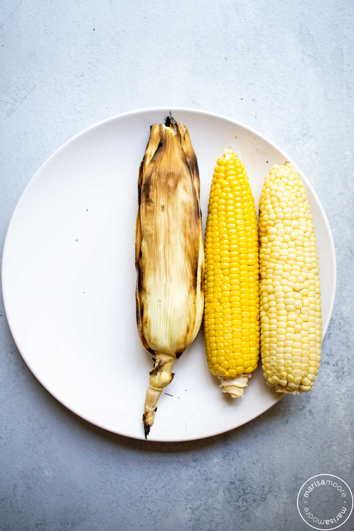 3 ears of grilled corn. One in the husk