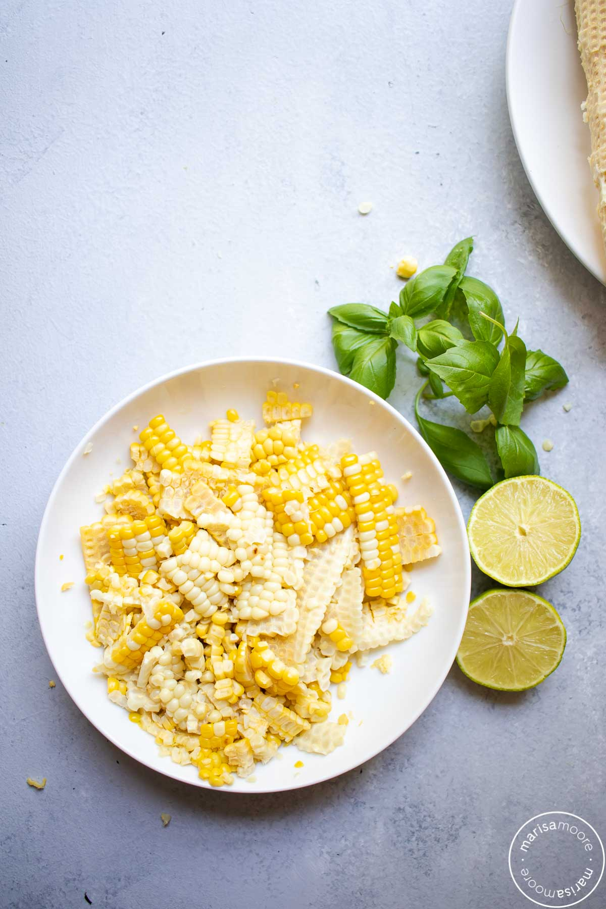 white and yellow corn in a bowl with basil and limes on the side