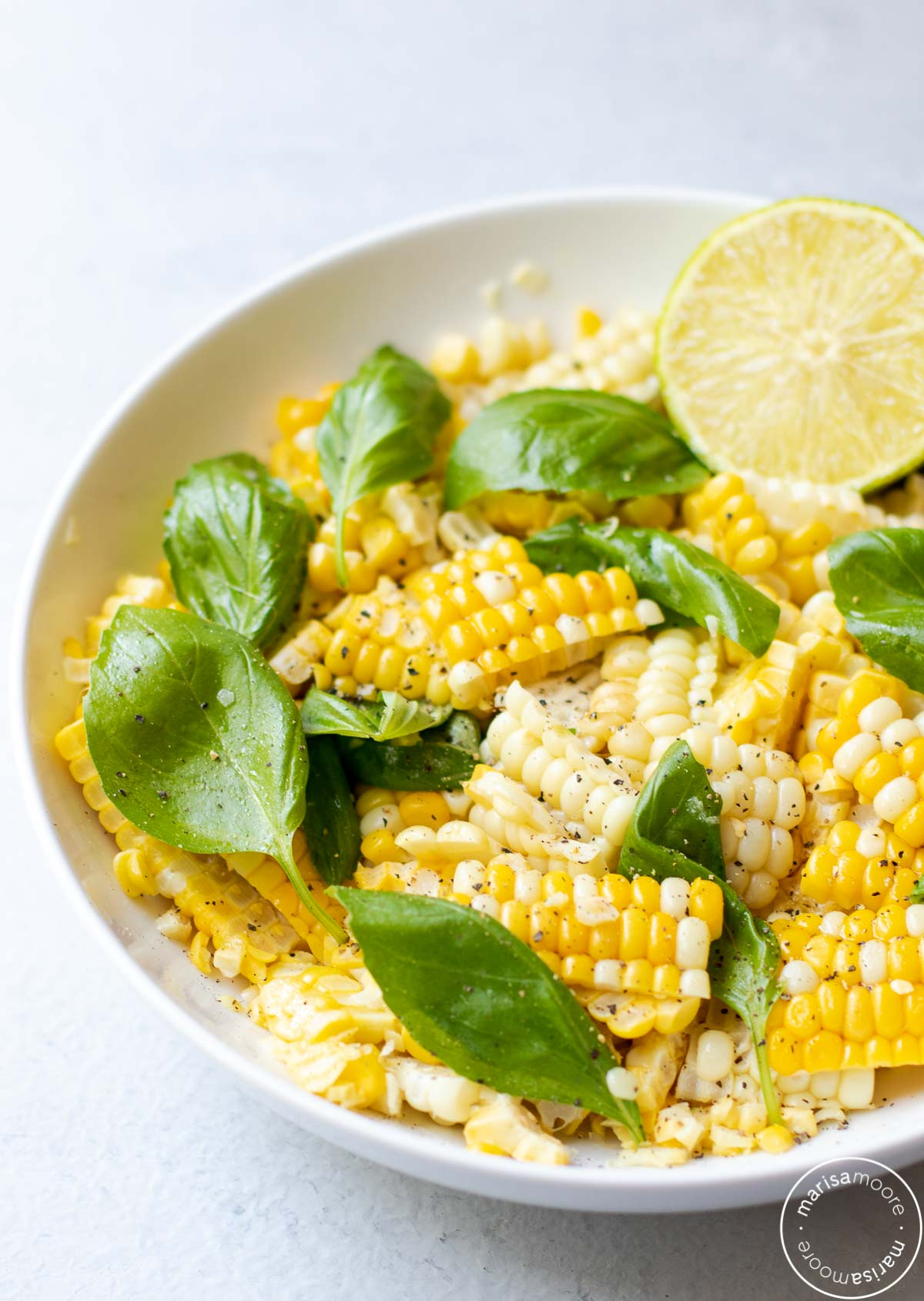 corn basil salad in white bowl with a cut lime