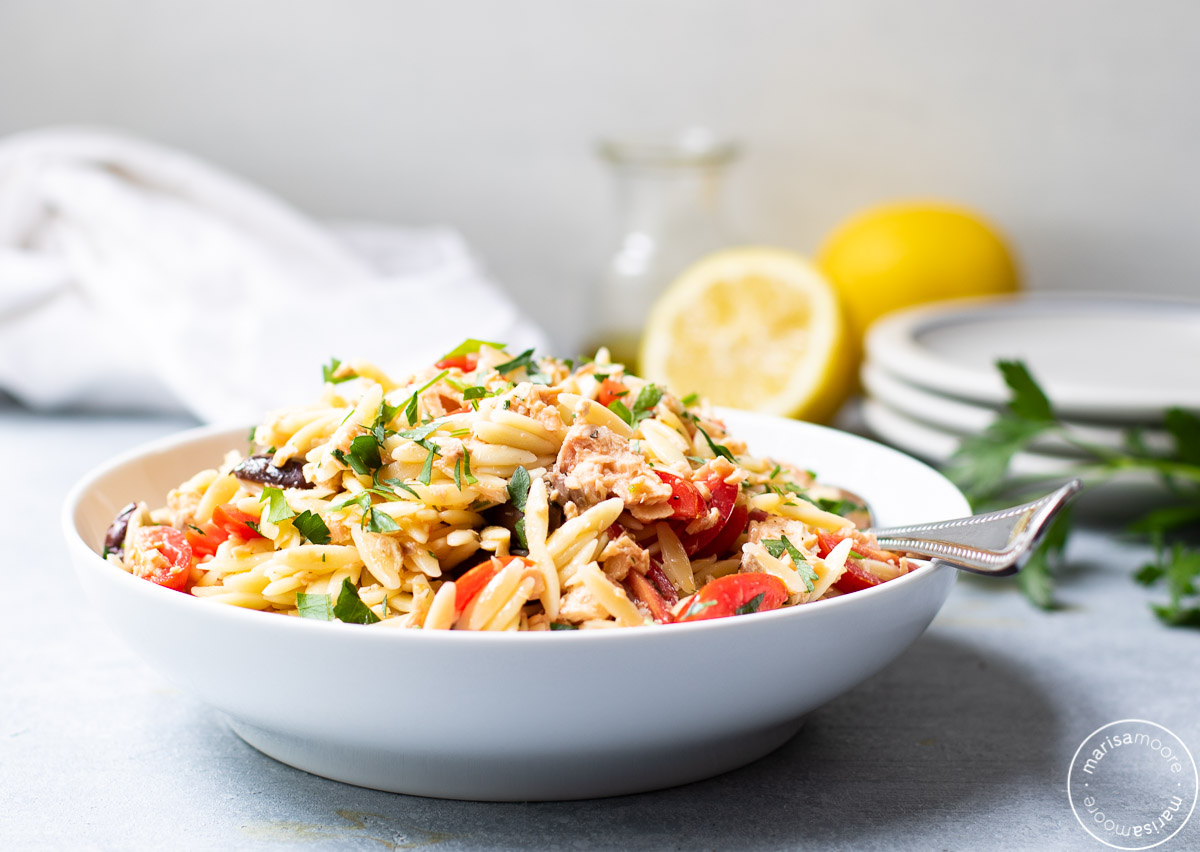 Salmon Orzo Salad in a bowl with lemons and plates in background