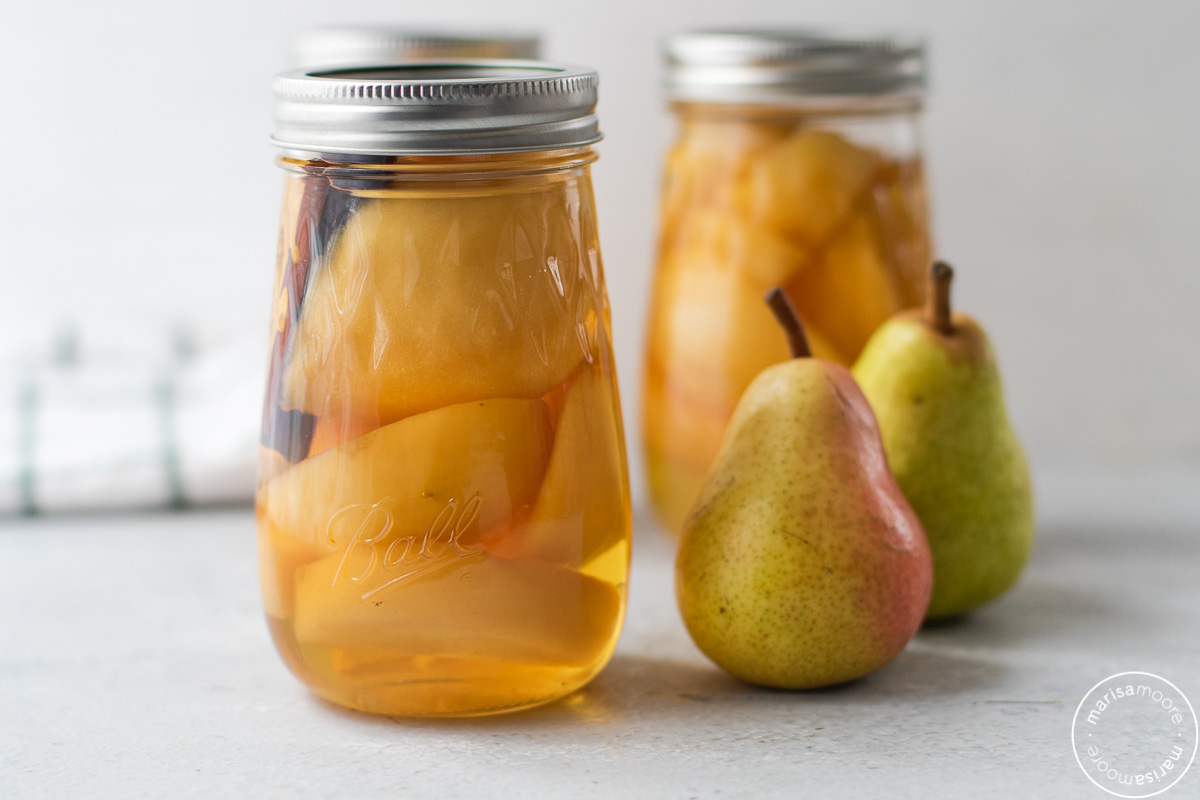 2 jars of canned pears with 2 fresh pears on the side