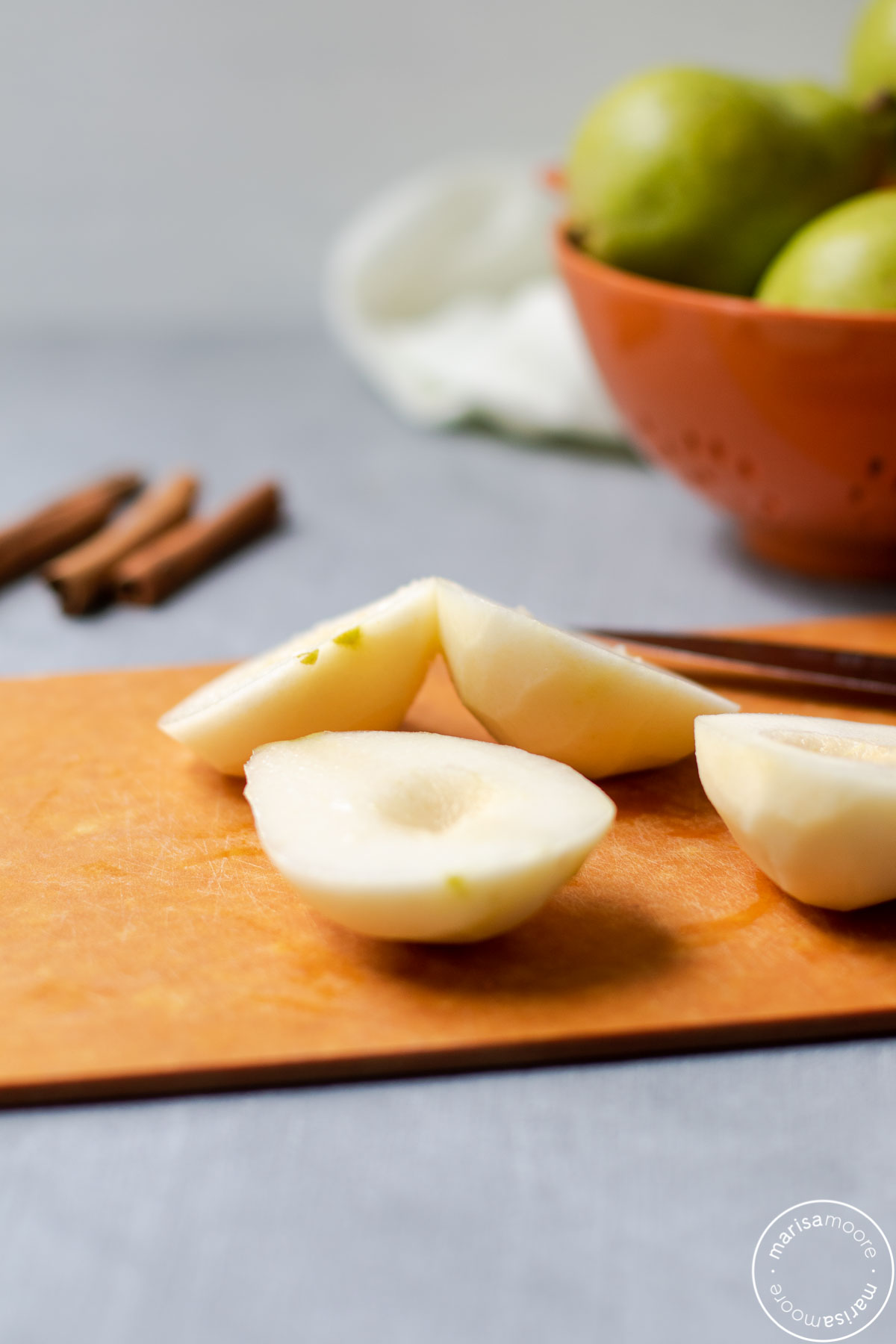 peeled, halved, and scooped pears on a cutting board with whole pears in background