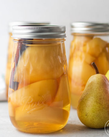 3 jars of canned pears with 2 fresh pears on the side