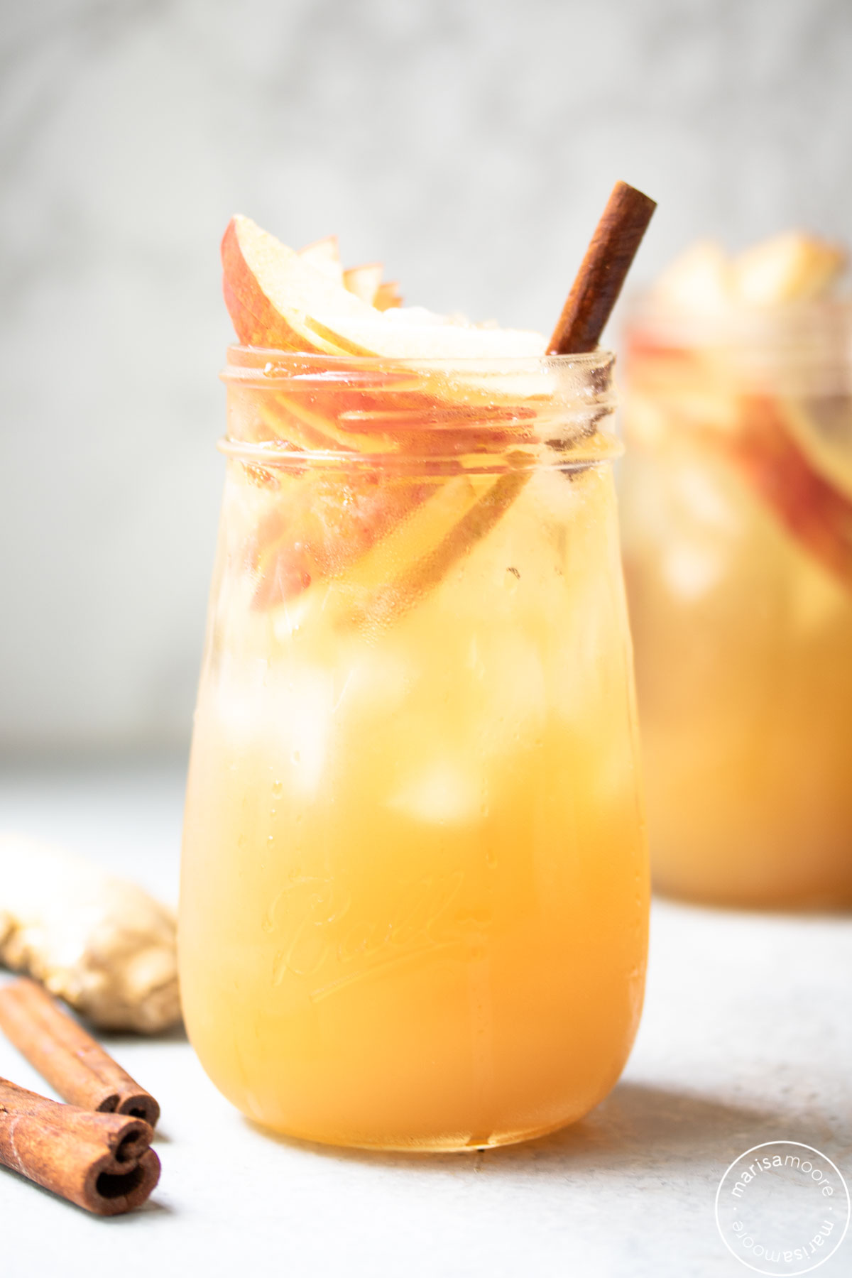 two fluted jars with the mocktail inside garnished with apple slices and cinnamon sticks and ginger in the background