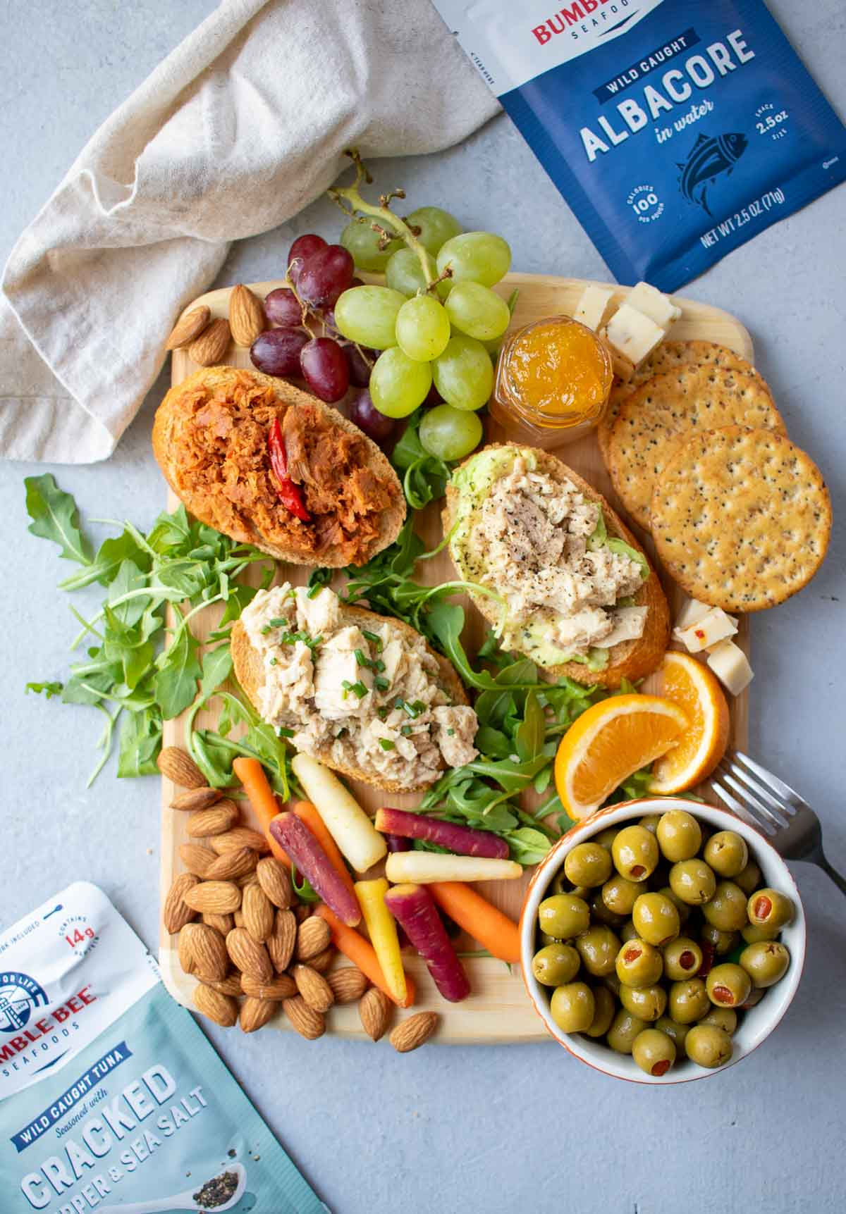 Snack board with tuna toasts, fruit, vegetables, nuts and packets of Bumble Bee Tuna