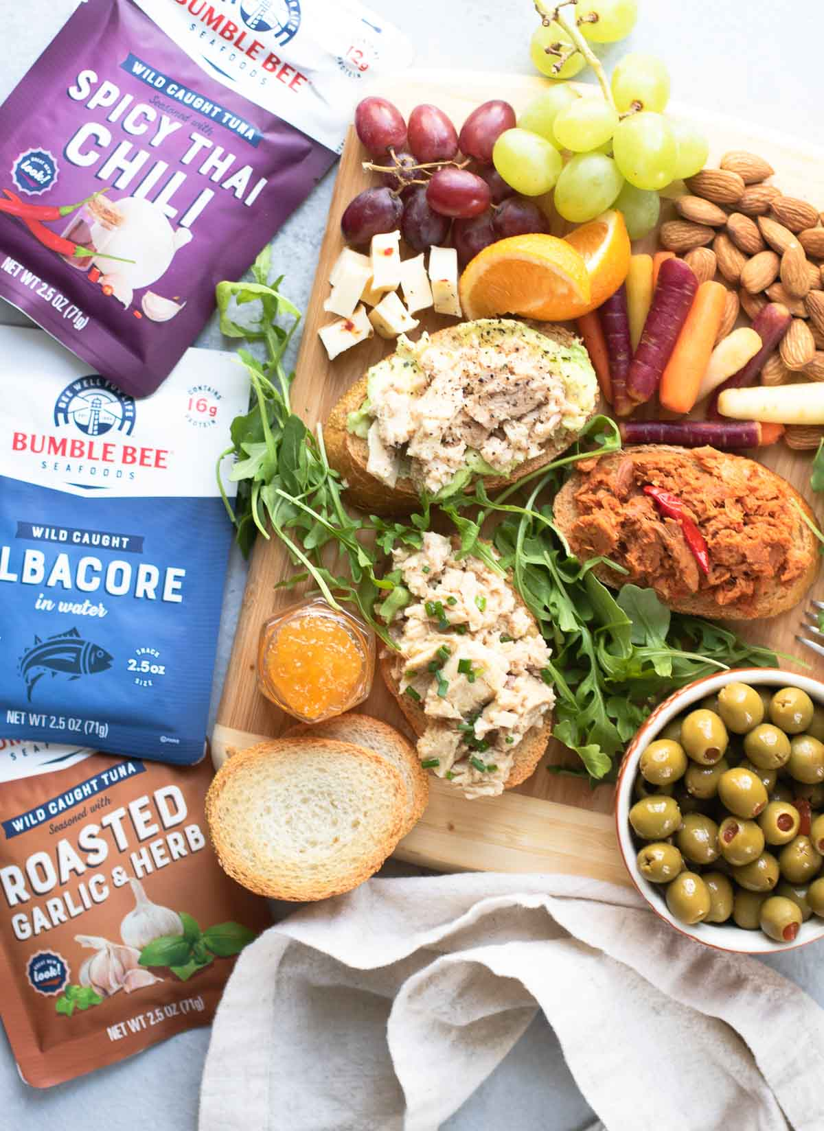 Crowded board with all tuna toasts and ingredients with packets of Bumble Bee Tuna on the side