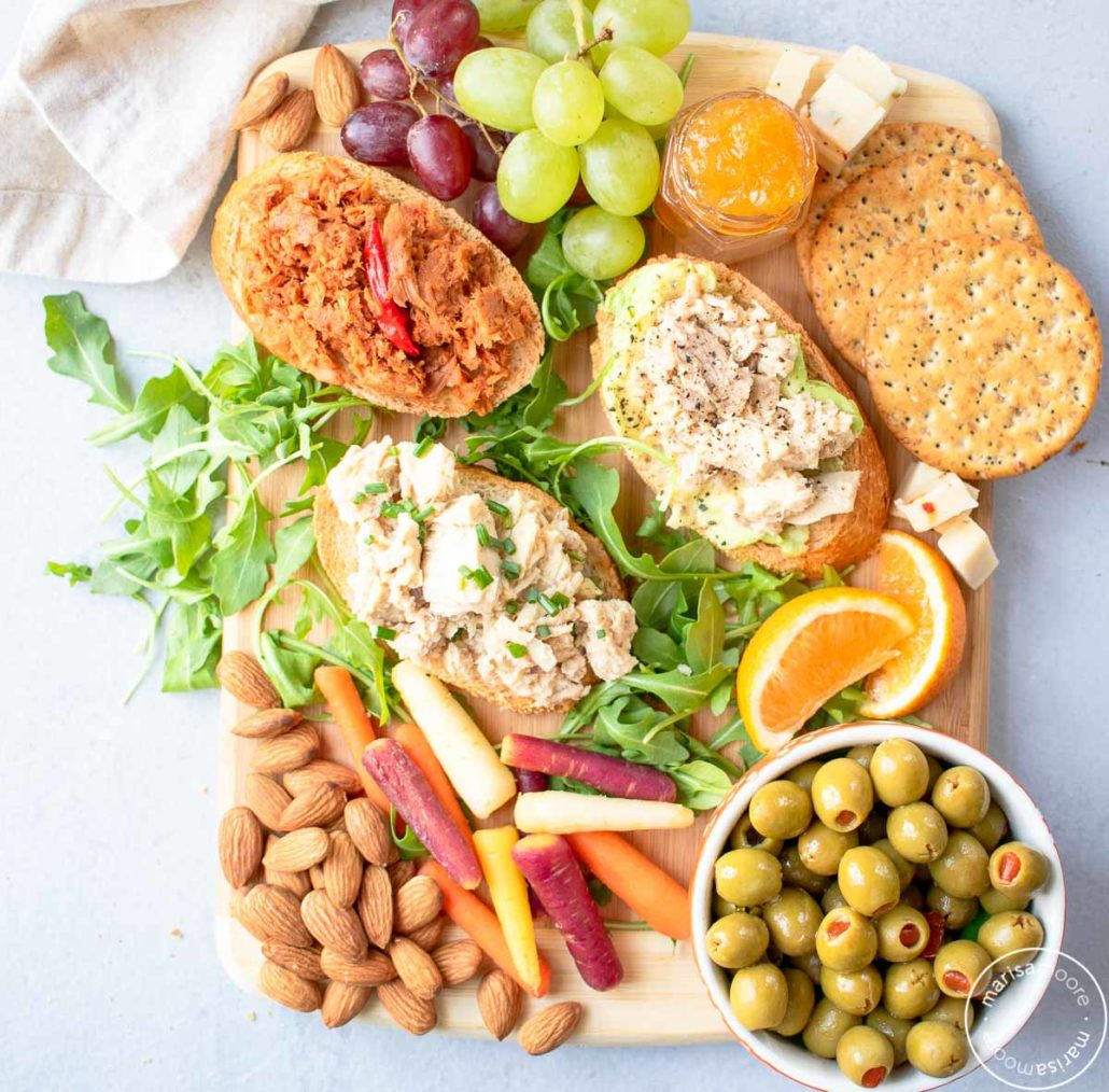 Snack board with tuna toasts, fruit, vegetables and nuts