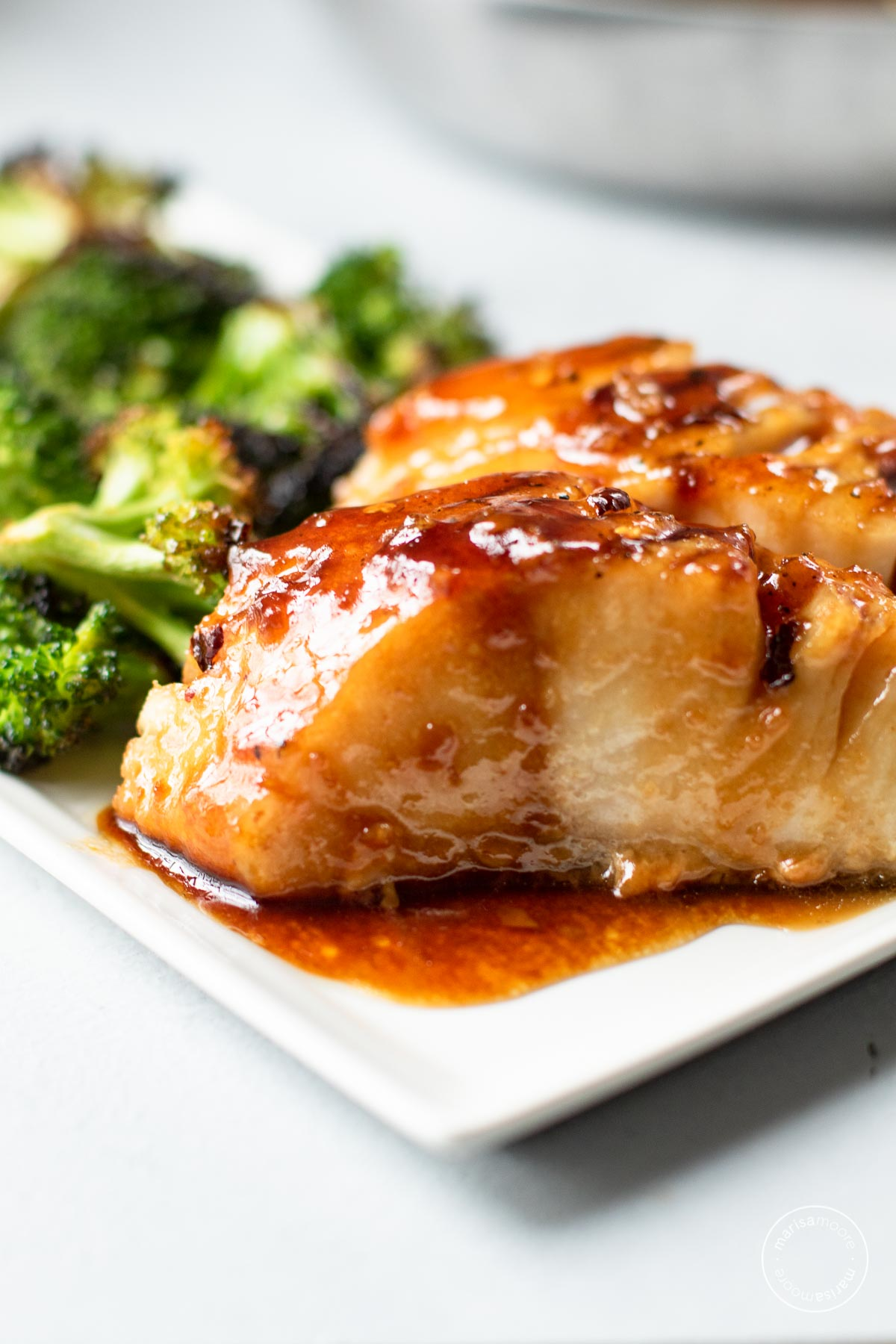 Honey garlic sablefish with broccoli on a white plate.