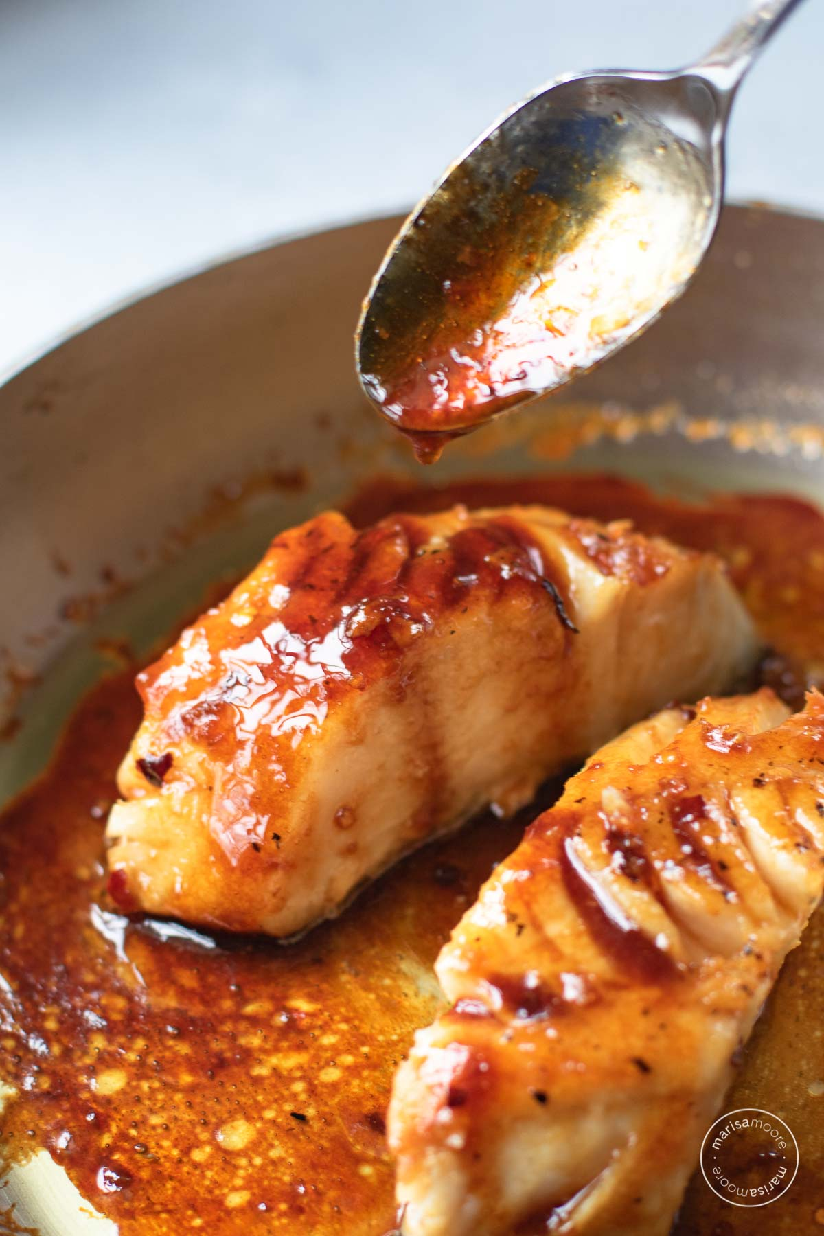 Close up of a spoon dripping glaze over the cooked sablefish in a skillet.