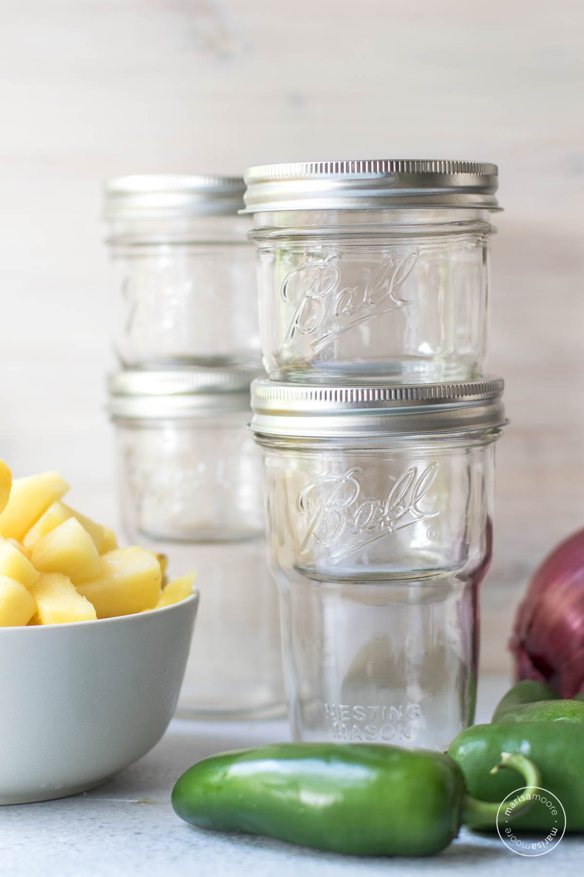 Ball nesting mason jars with a bowl of pineapple, jalapeno and red onion