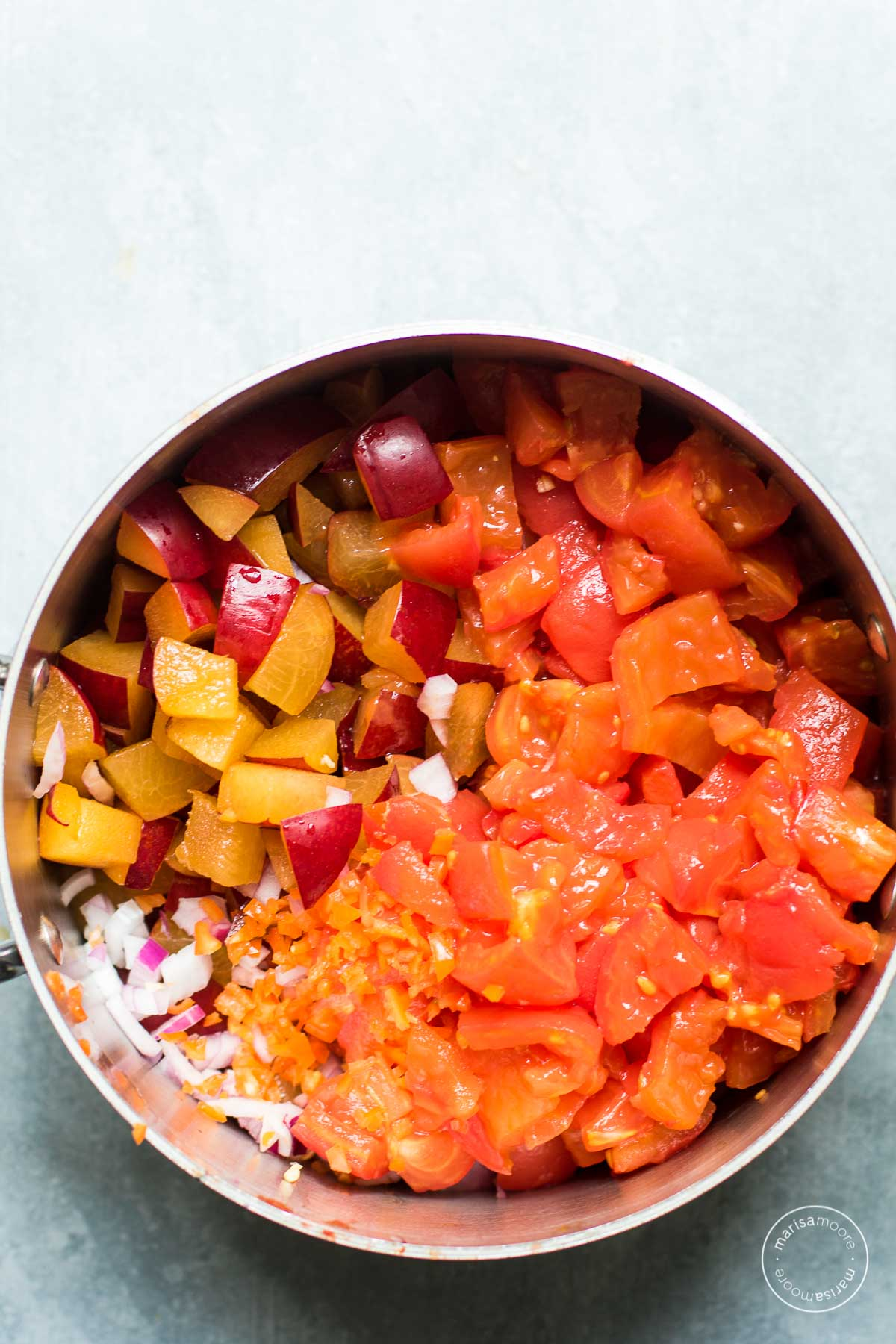 stock pot with chopped plums, tomatoes, red onion
