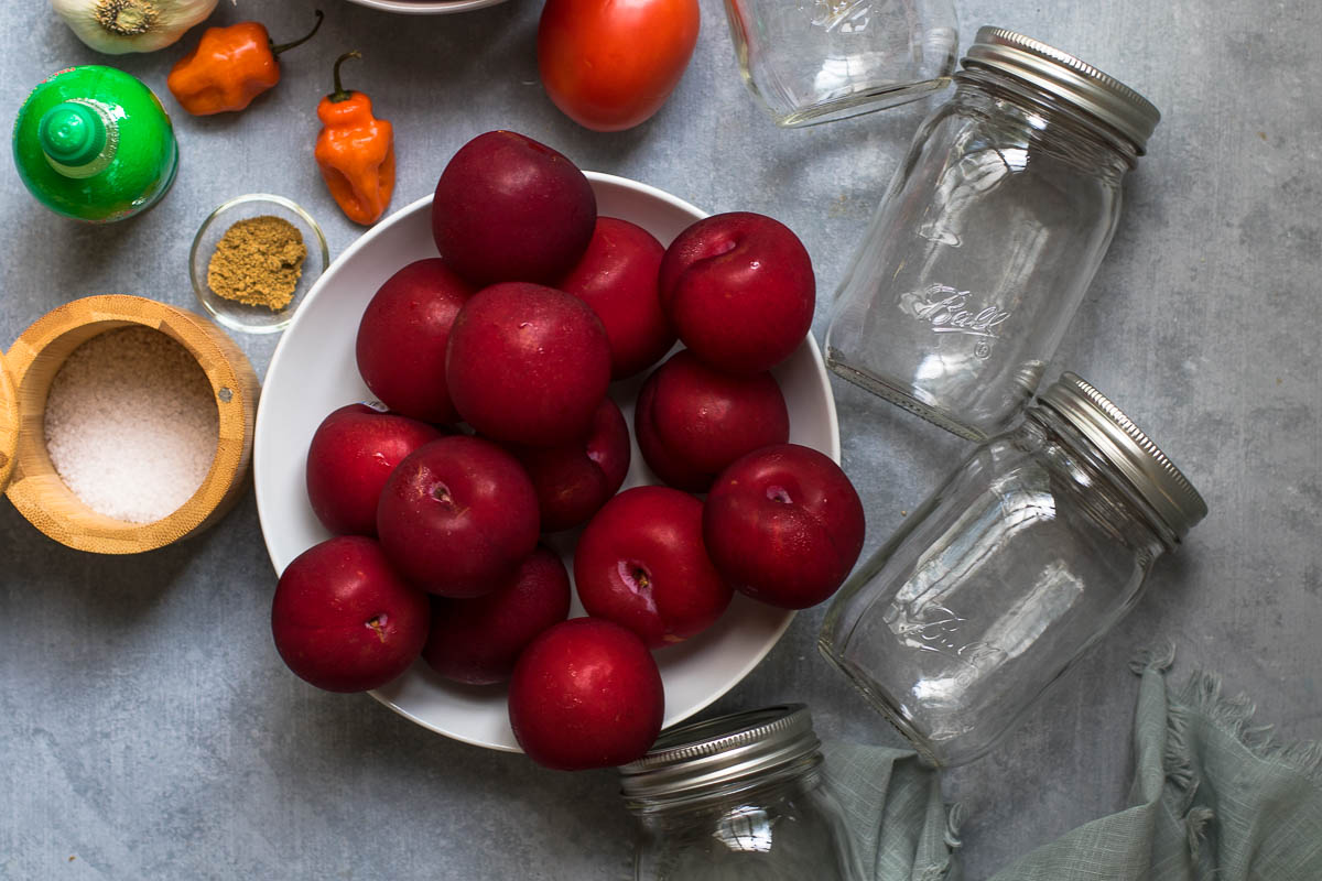 Ball jars with a bowl of plums, salt, habaneros, bottled lime juice and ground coriander
