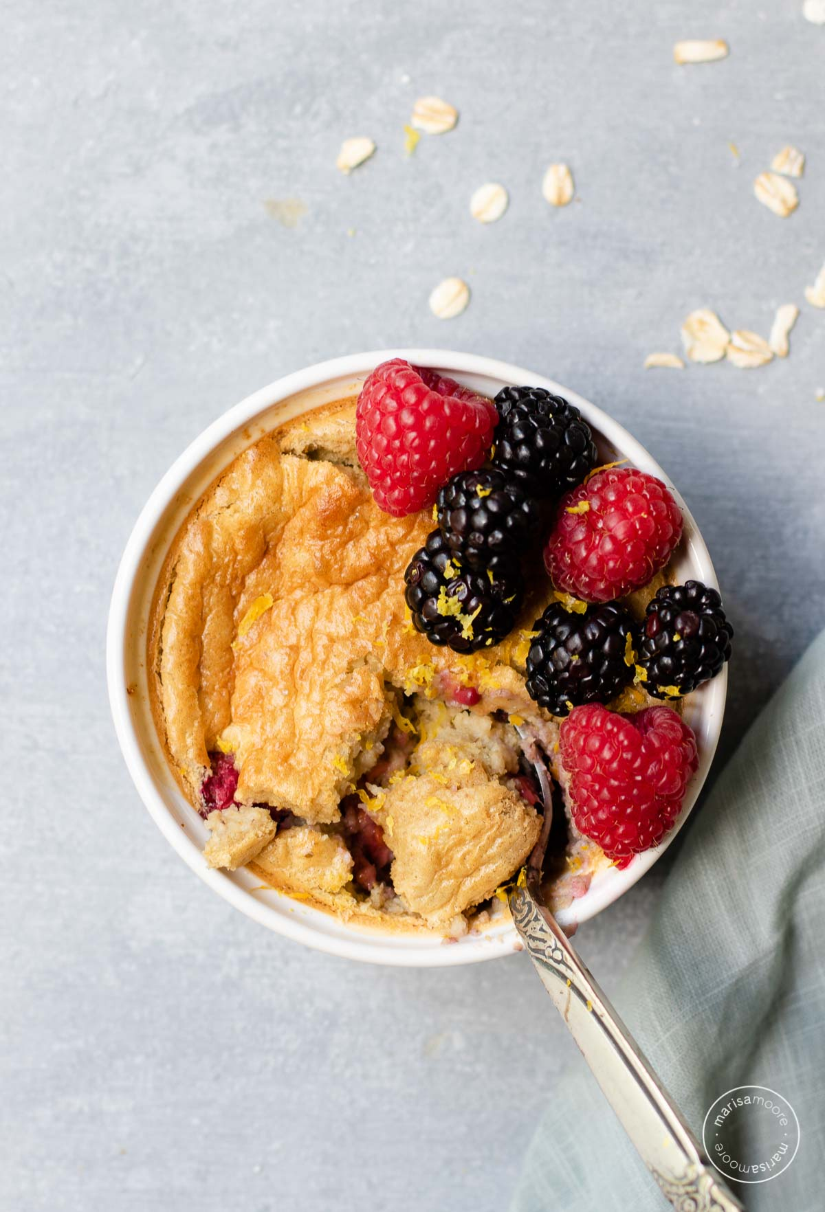 Baked oats with berries in a white ramekin with a spoon
