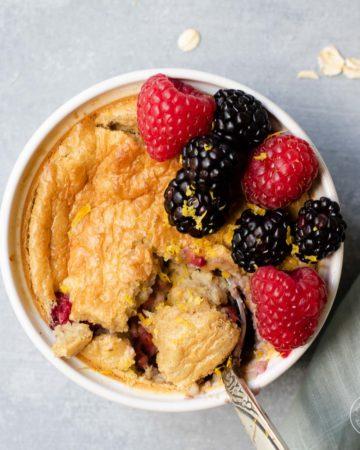 Baked oats with berries in a white ramekin