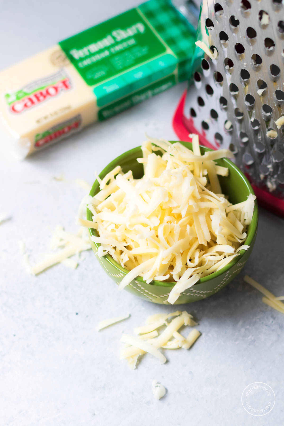 Shredded cheese in a green bowl with a cheese grater in the background