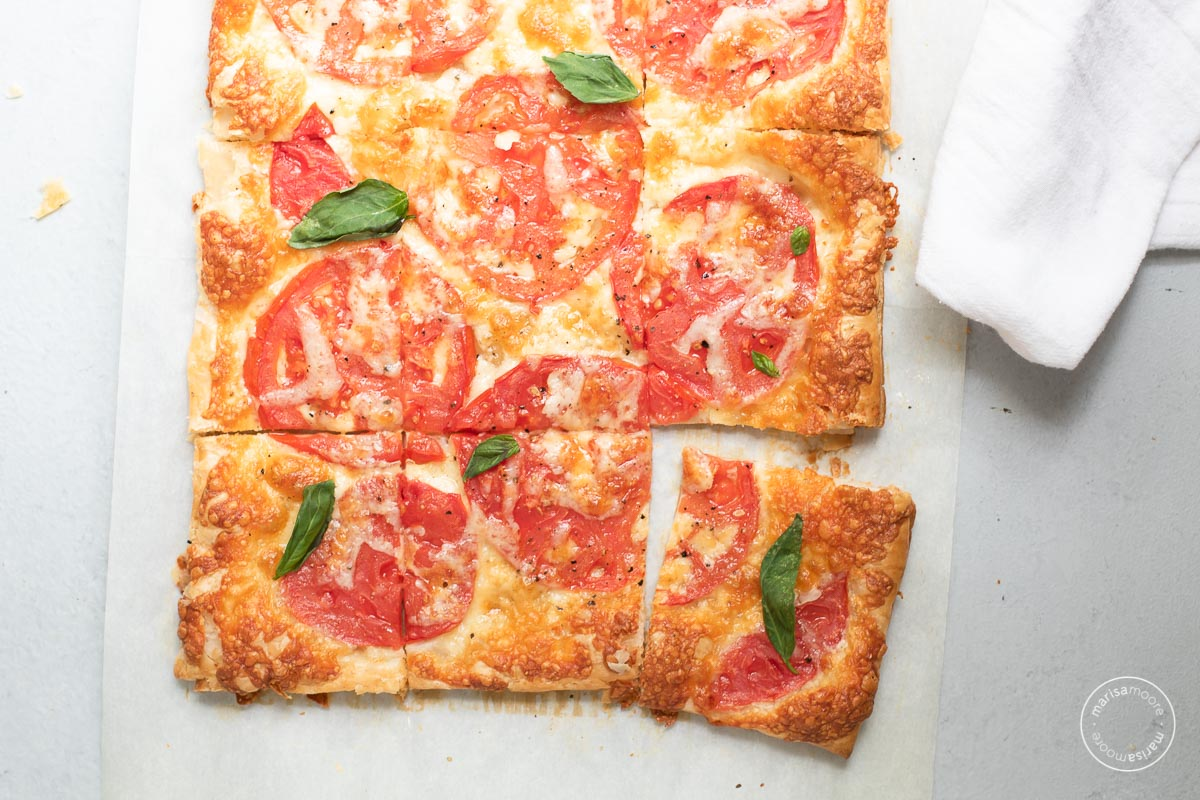 Tomato Cheese tart cut into squares on a grey background