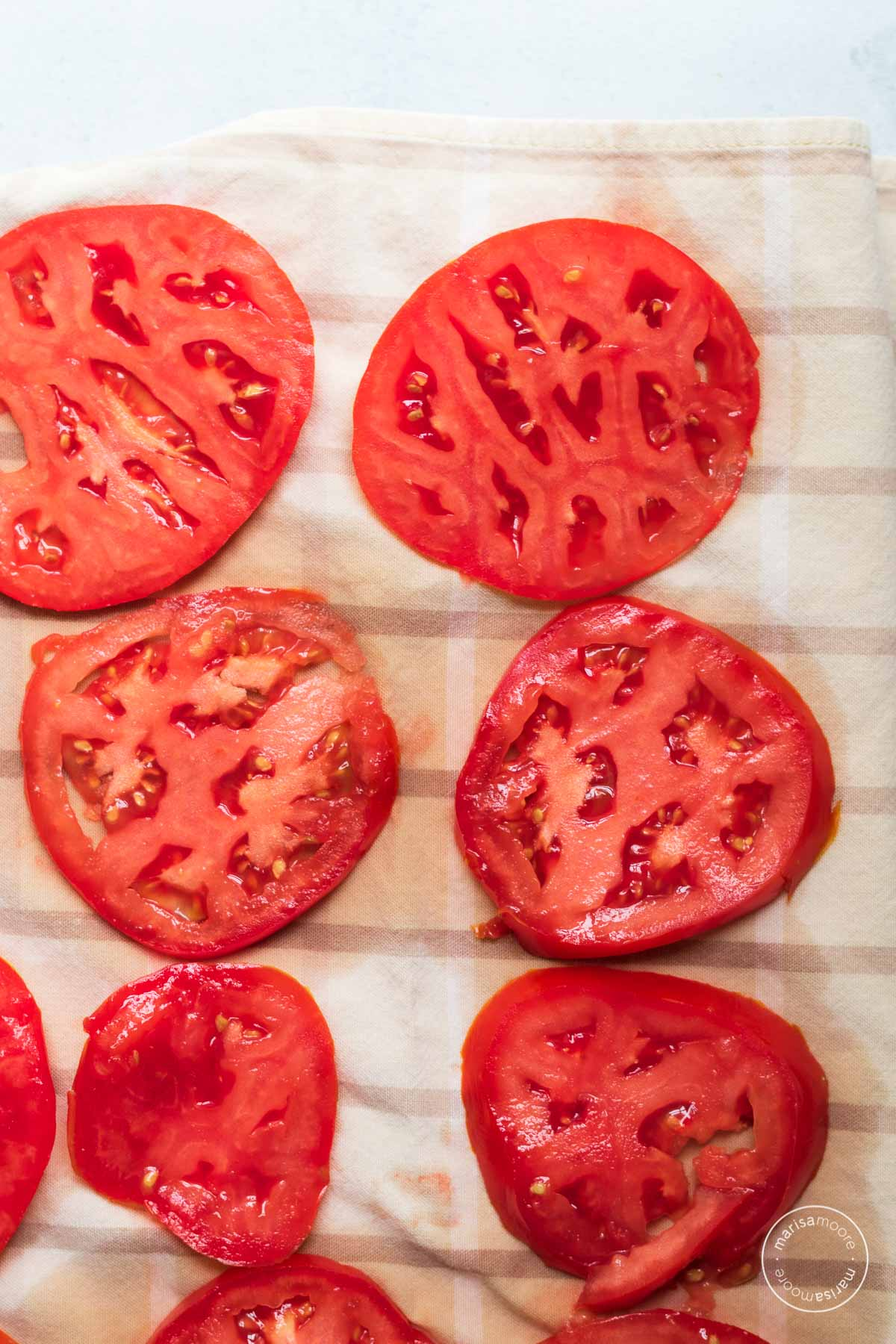 Red tomato slices on a cloth napkin draining