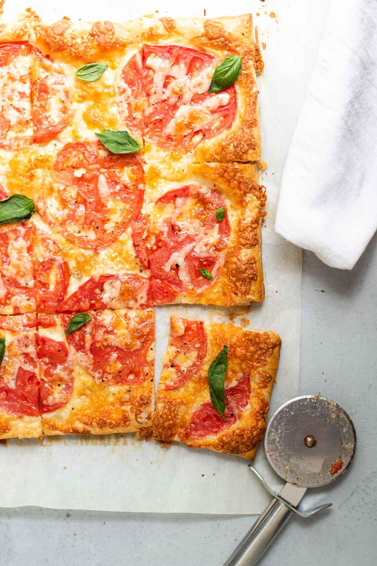 Tomato Cheese Tart with a white napkin and pizza wheel