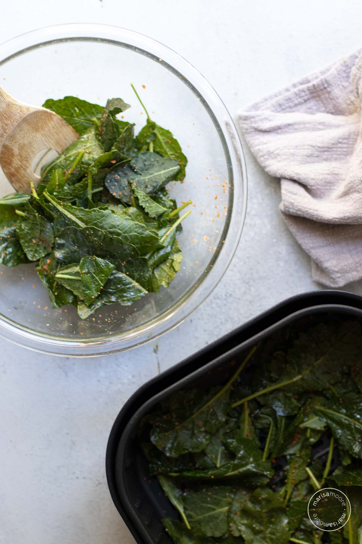 glass bowl with oiled and seasoned kale chips and an air fryer basket with a single layer of kale inside.