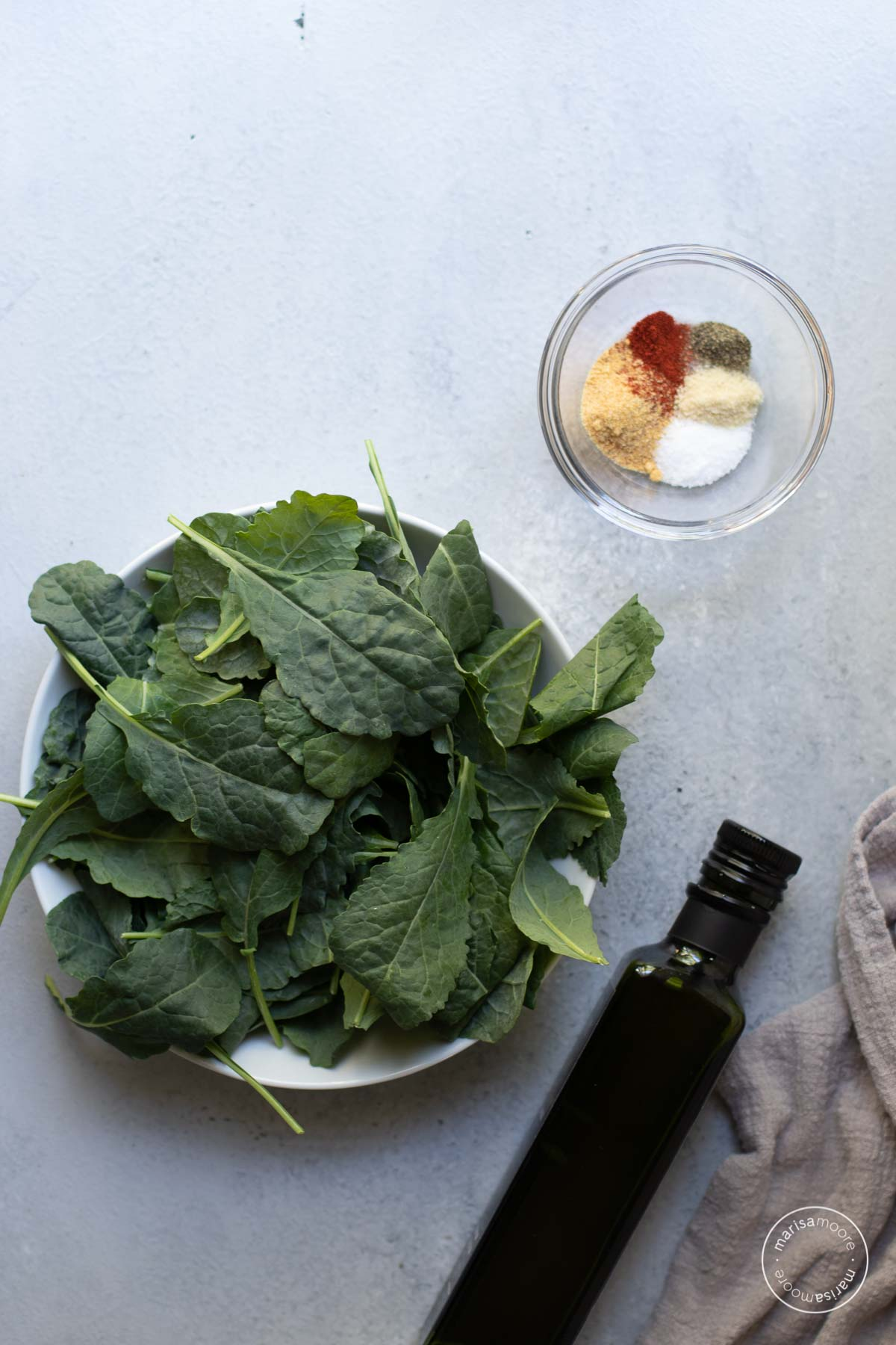 Ingredients on a gray background. Includes kale in a white bowl, spices in a clear bowl and a bottle of olive oil.
