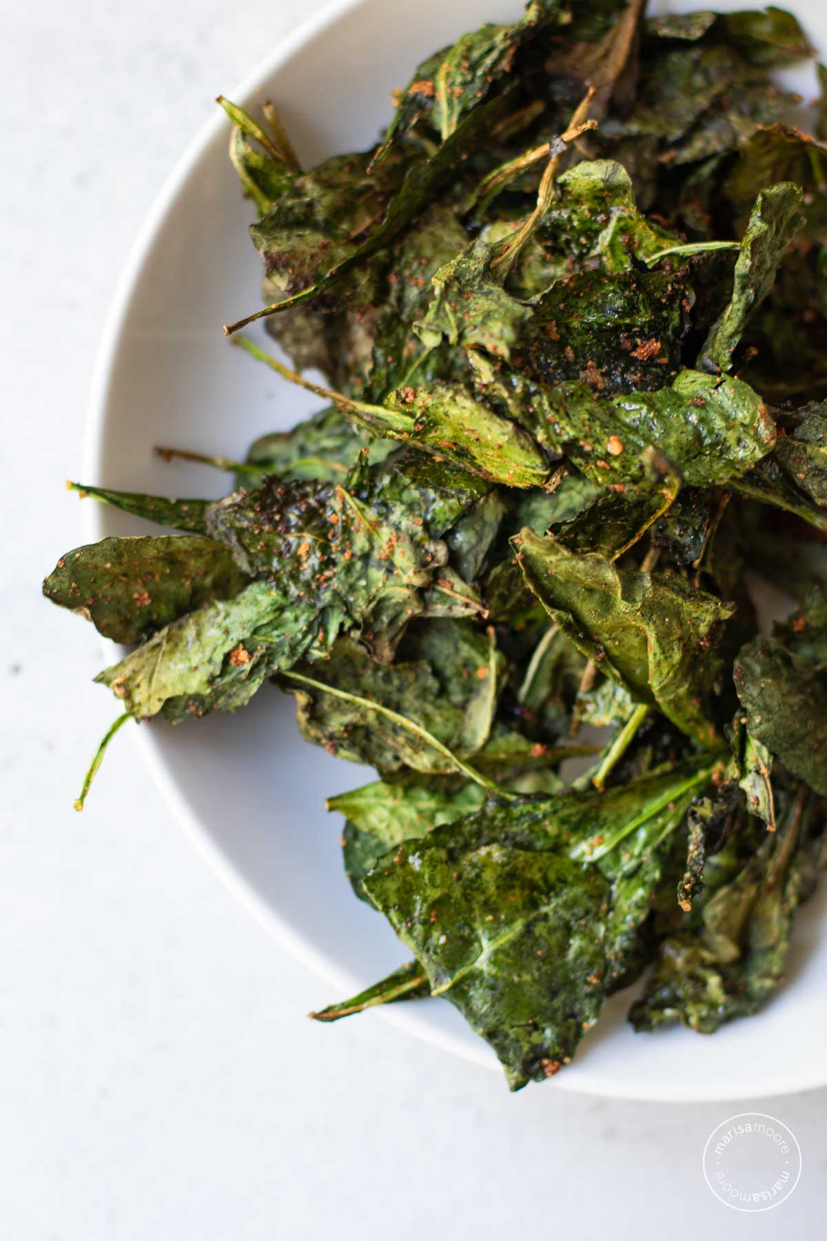 Overhead shot of seasoned kale chips in a white bowl.