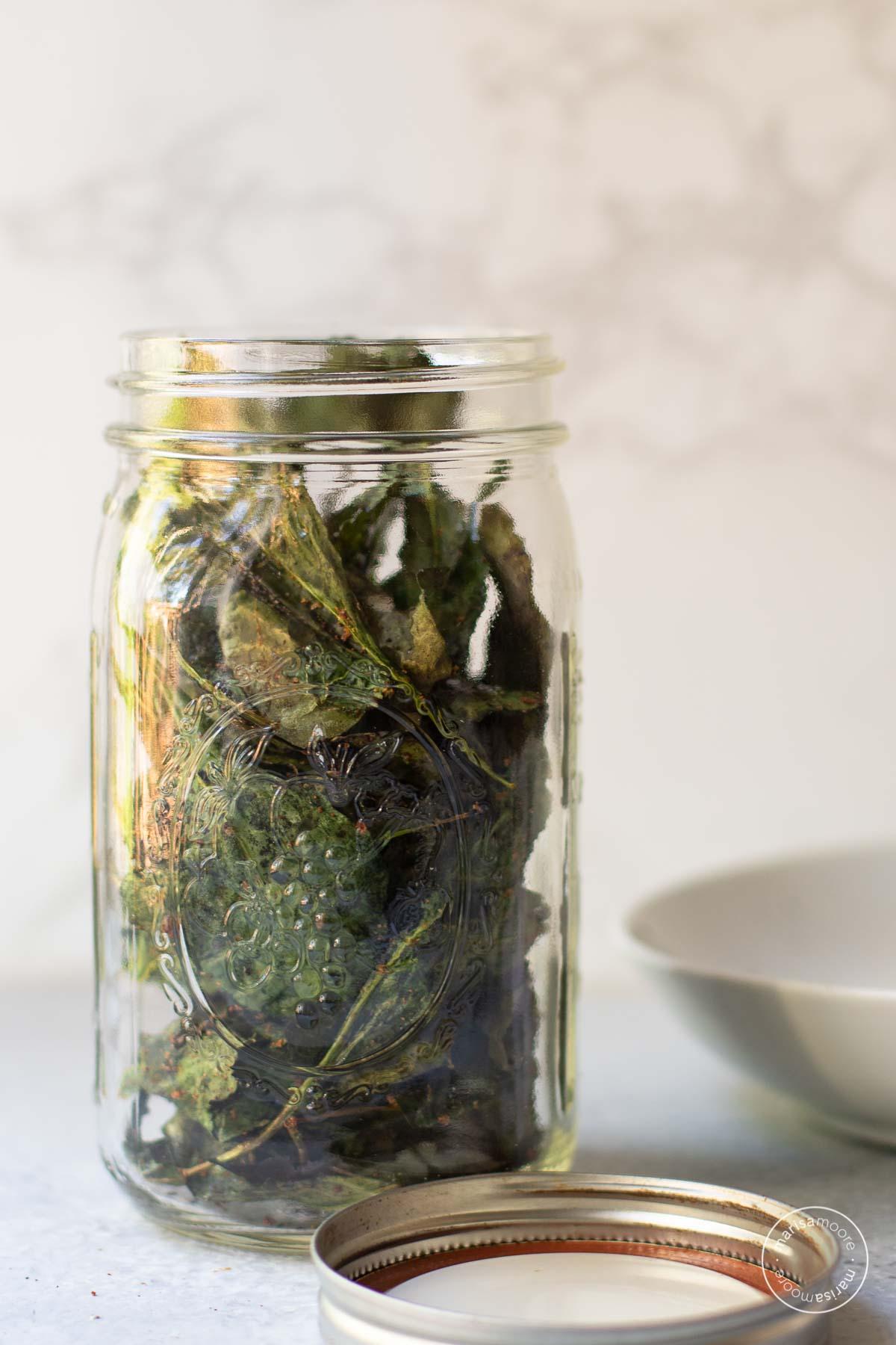 Quart size jar filled with kale chips.