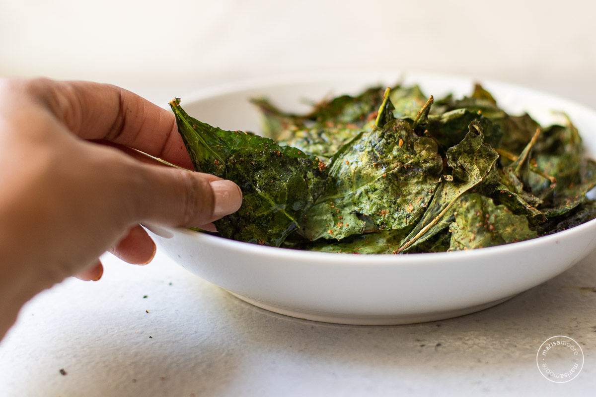 Kale chips in a white bowl with Marisa's hand reaching for one chip.